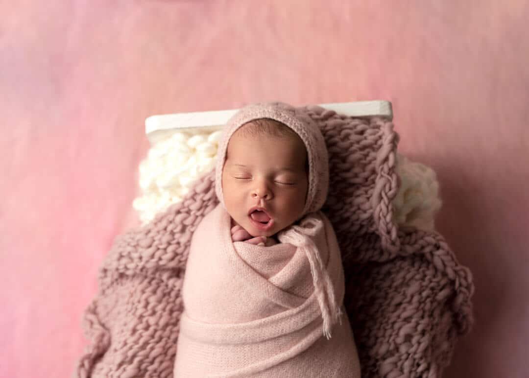 newborn daughter in pink background yawning. iris lane photography akron canton ohio