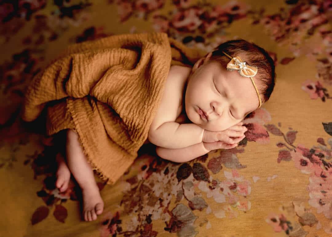 newborn girl on yellow floral backdrop sleeping. iris lane photography akron canton green hartville ne ohio