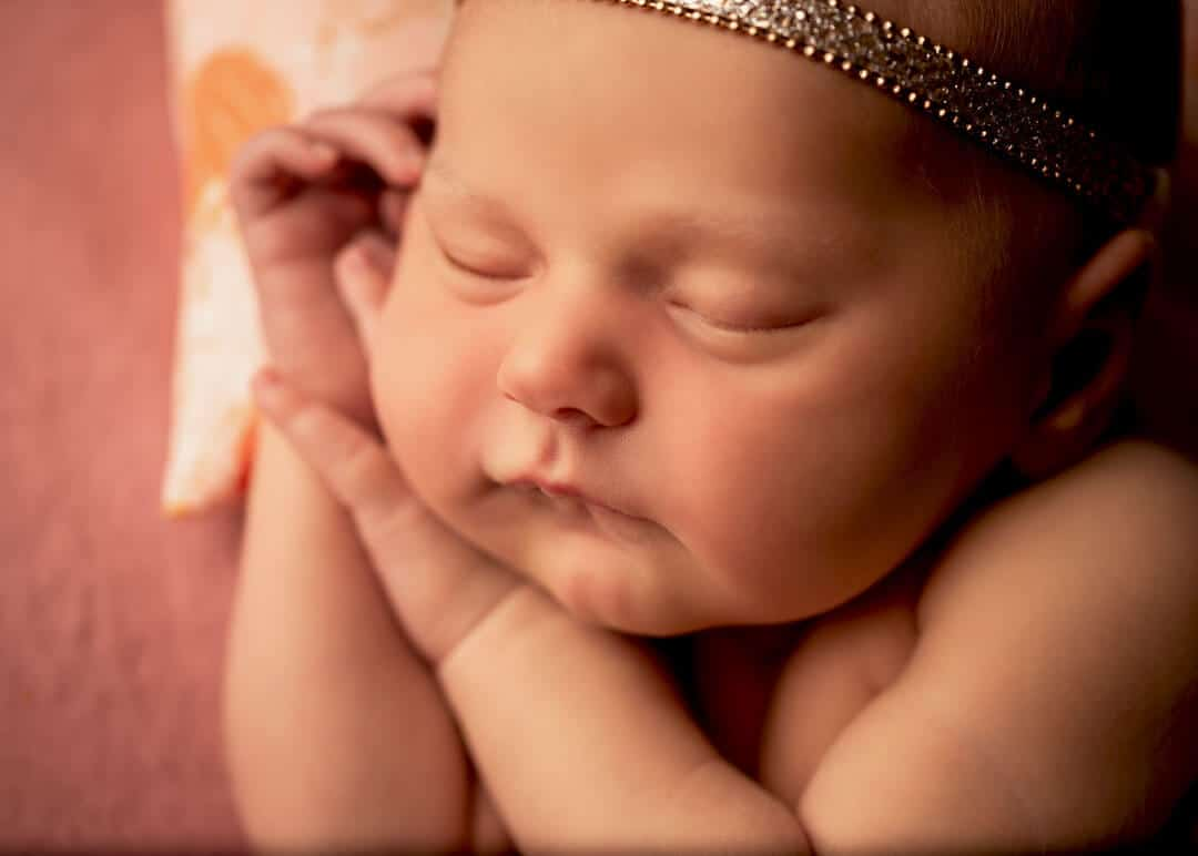 newborn baby girl sleeping on pink backdrop and pink pillow.  iris lane photography akron canton green hartville ne ohio