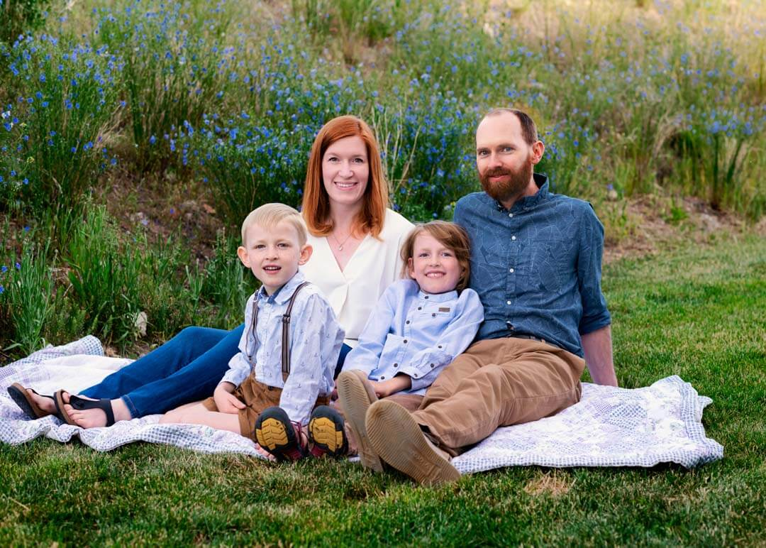 family of 4 sitting on blanket in grass. iris lane photography akron canton ohio