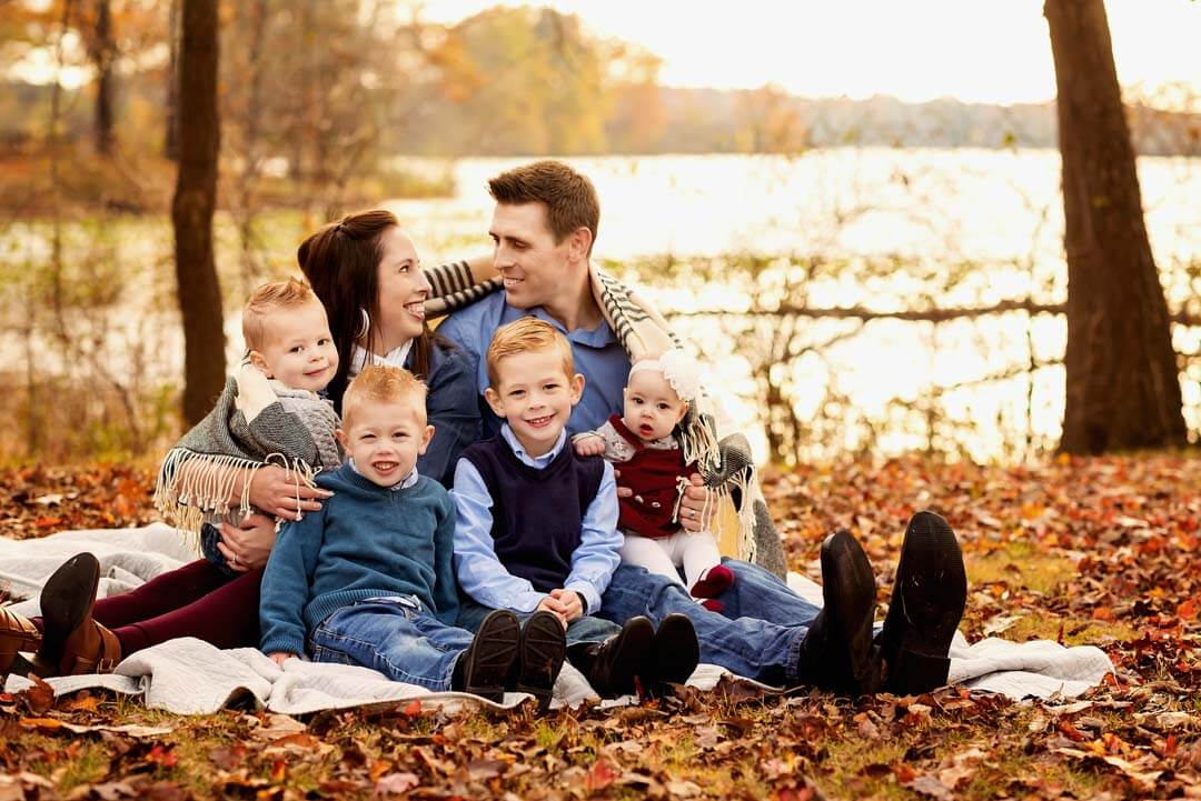 family of 6 sitting outdoors on blanket on leaves fall session.  iris lane photography akron canton green hartville ne ohio