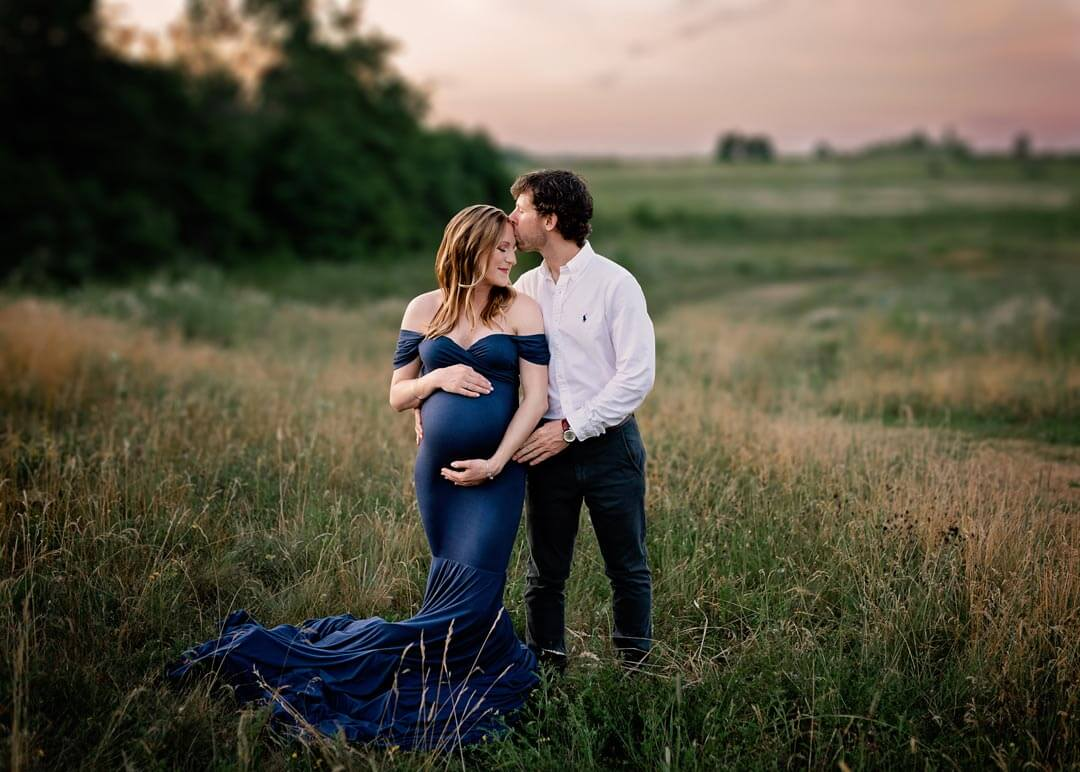 Pregnant woman hands on belly standing in field at sunset with blue dress with husband standing next to her. Iris Lane Photography Akron Canton Cleveland Youngstown NE OHIO maternity newborn photographer