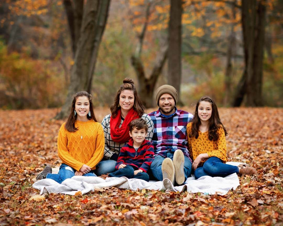 family sitting in fall leaves. Iris lane photography family photo session fall akron canton hartville ohio