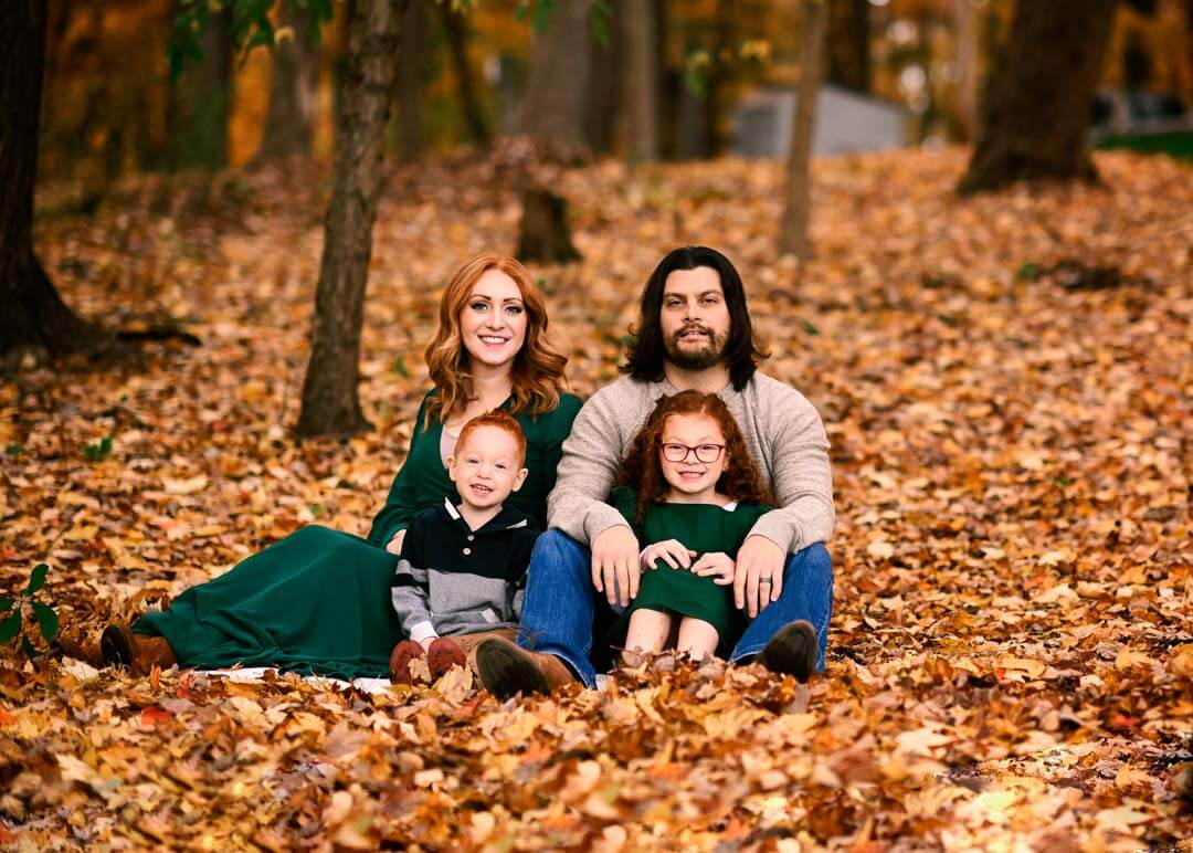 family of 4 sitting in the leafs fall session outdoors.  iris lane photography akron canton green hartville ne ohio
