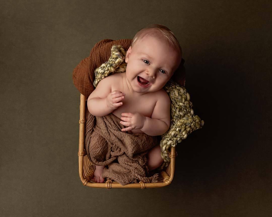 baby boy sitting in basket laughing. iris lane photography akron canton ohio